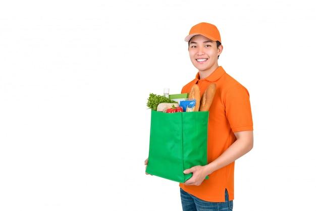 Lächelnder asiatischer lieferbote, der einkaufstasche der lebensmittel trägt