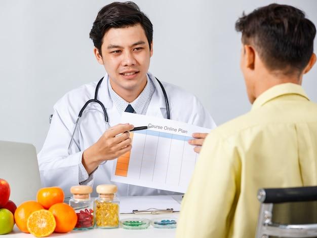Lächelnder asiatischer männlicher ernährungsberater, der dem patienten ein diagramm zeigt, während er die lösung für eine gesunde ernährung auf weißem hintergrund erklärt
