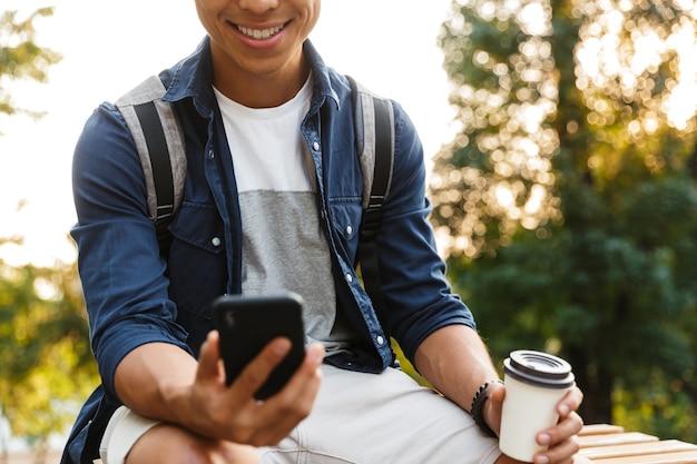 Lächelnder asiatischer männlicher student, der smartphone und kaffeetrinken beim sitzen im park verwendet