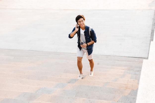 Lächelnder asiatischer mann, der auf handy spricht, während er oben draußen mit tasse kaffee geht