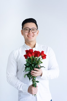 Lächelnder asiatischer mann, der bündel rosen hält