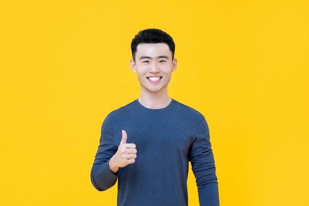 Lächelnder asiatischer mann, der die daumen oben lokalisiert gibt