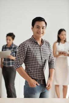 Lächelnder asiatischer mann, der dokumentenordner, mit kollegen im hintergrund steht und hält
