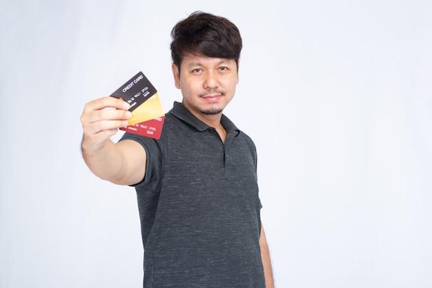 Lächelnder asiatischer mann, der drei kreditkarte hält