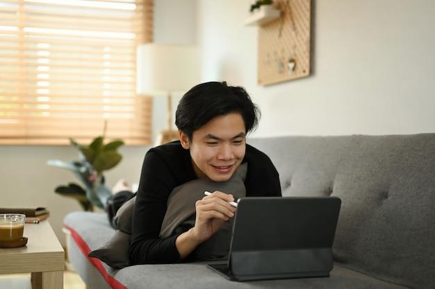 Lächelnder asiatischer mann mit computertablette auf dem sofa zu hause.