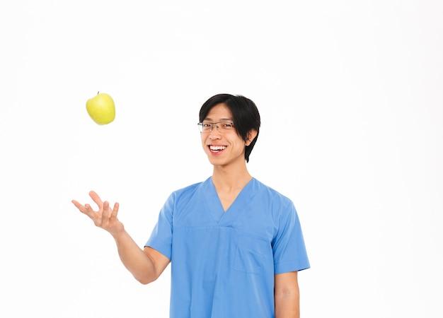 Lächelnder asiatischer mannarzt, der uniform trägt, die lokal über weißer wand steht und grünen apfel zeigt