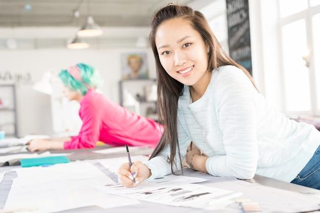 Lächelnder asiatischer schneider im atelier
