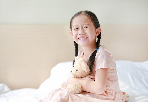 Lächelnder asiatischer umarmungsteddybär des kleinen mädchens, der zu hause auf dem bett sitzt