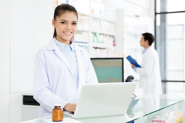 Lächelnder asiatischer weiblicher apotheker, der in der apotheke arbeitet