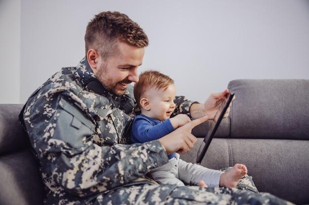 Lächelnder attraktiver bärtiger soldat, der mit seinem kleinen sohn auf sofa im wohnzimmer sitzt und spiele auf tablette spielt.