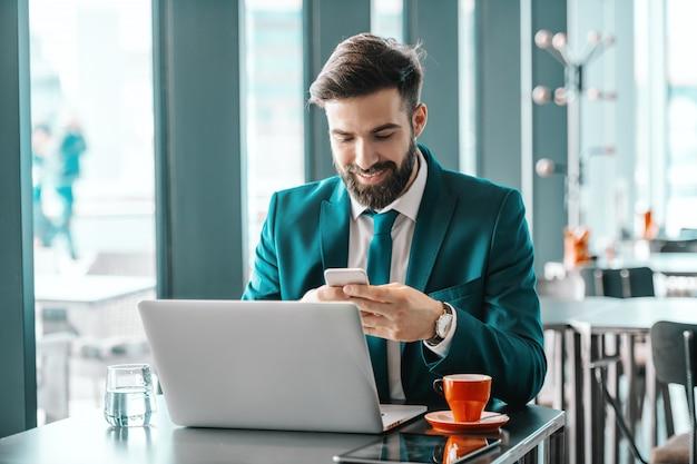 Lächelnder attraktiver ehrgeiziger geschäftsmann im türkisfarbenen anzug, der smartphone zum lesen oder schreiben der nachricht beim sitzen im café verwendet. auf dem schreibtisch glas wasser, laptop, kaffee und tablet. wenn sie einen job wählen