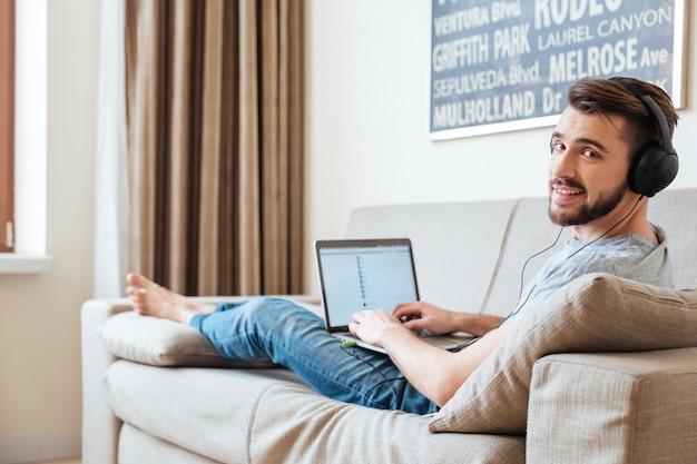 Lächelnder attraktiver junger mann, der auf dem sofa liegt und zu hause musik vom laptop hört