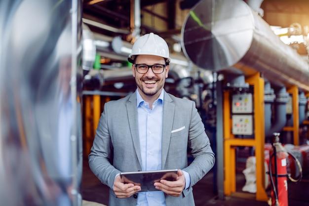 Lächelnder attraktiver kaukasischer aufseher im grauen anzug und mit dem weißen helm auf kopf, der tablette hält, während er im kraftwerk steht.