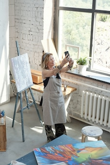 Lächelnder attraktiver künstler in der schürze, die selfie auf eigenem bild im kunststudio nimmt