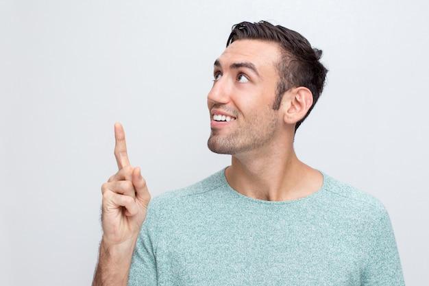 Lächelnder attraktiver mann, der nach oben zeigt