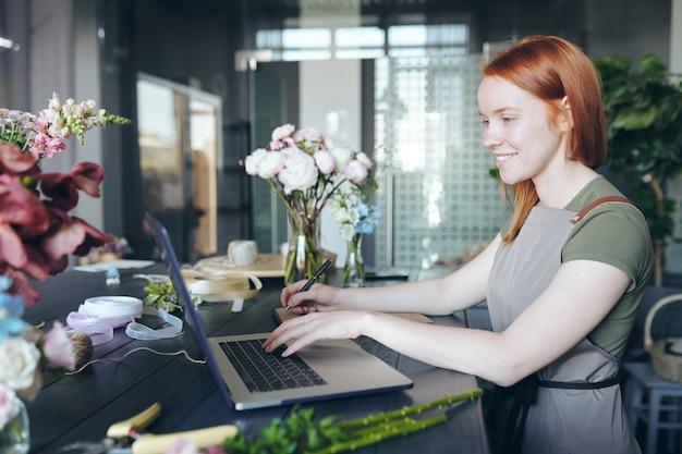 Lächelnder attraktiver weiblicher florist mit roten haaren, die an der theke mit blumen und verpackungsgegenständen stehen und laptop verwenden, während liste der notwendigen blumen machen
