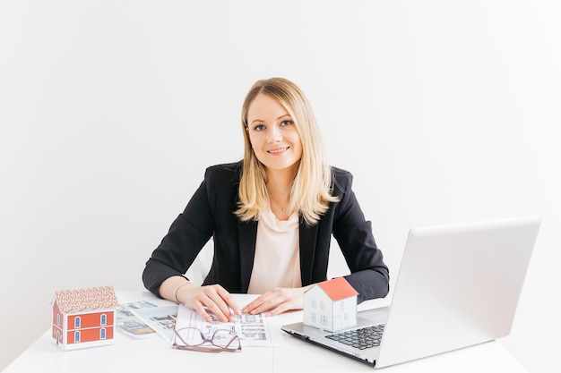 Lächelnder attraktiver weiblicher immobilienmakler, der im büro sitzt