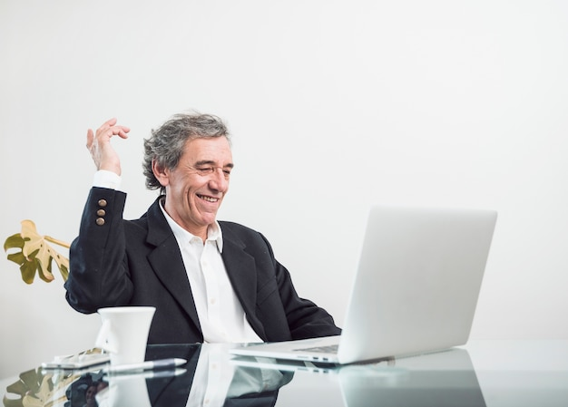 Lächelnder aufgeregter älterer mann, der am arbeitsplatz betrachtet laptop sitzt
