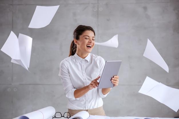 Lächelnder aufgeregter weiblicher architekt, der tablette innen verwendet. überall um sie herum sind papierkram und blaupausen.