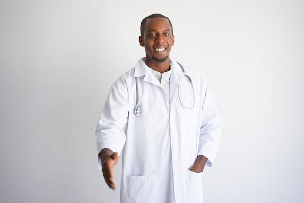 Lächelnder ausdehnender arm des schwarzen männlichen doktors für händedruck.