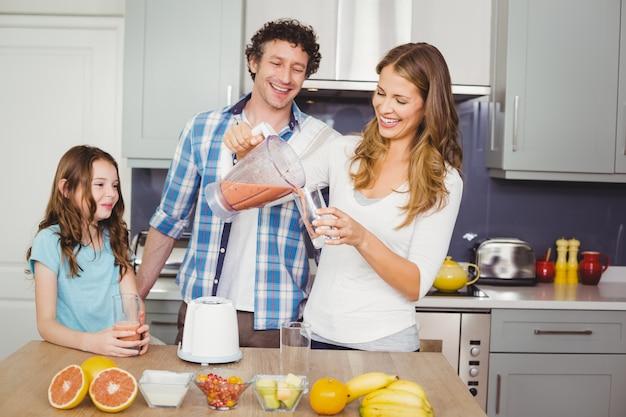 Lächelnder auslaufender fruchtsaft der mutter in einem glas mit familie