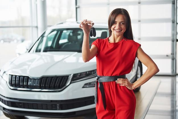 Lächelnder autoverkäufer, der ihre neuen autoschlüssel, ihr autohaus und ihr verkaufskonzept übergibt. glückliches mädchen der käufer