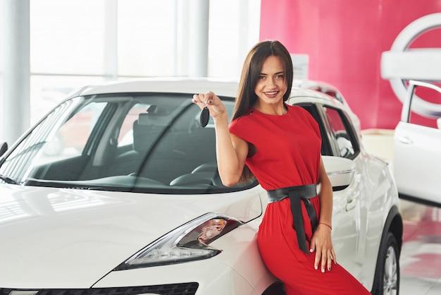 Lächelnder autoverkäufer, der ihre neuen autoschlüssel, ihr autohaus und ihr verkaufskonzept übergibt.