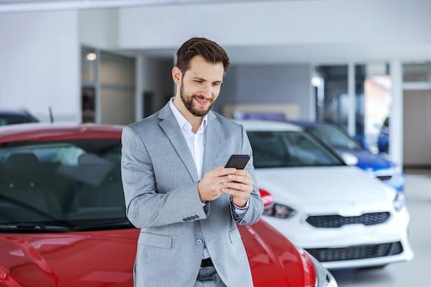 Lächelnder autoverkäufer, der im autosalon steht und telefon benutzt, um auf die nachricht eines kunden zu antworten.