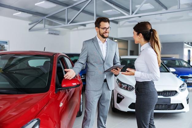 Lächelnder autoverkäufer, der mit kunden im autosalon steht und autos zum verkauf zeigt.