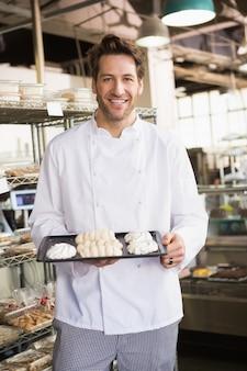 Lächelnder bäcker, der baisertablett hält