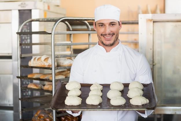 Lächelnder bäcker, der behälter des rohen teigs hält