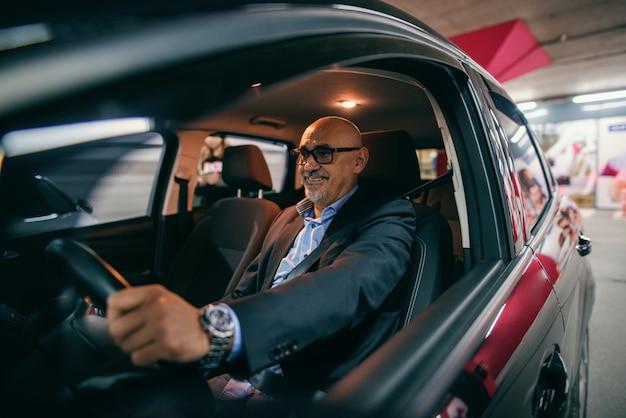 Lächelnder bärtiger älterer erwachsener, der auto nachts fährt.