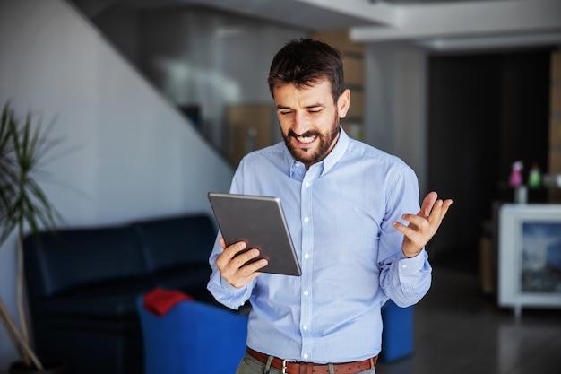 Lächelnder bärtiger chef, der in der lobby der großen lieferfirma steht und tablette betrachtet. er überwacht die lieferung.