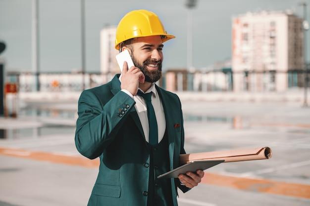 Lächelnder bärtiger erfolgreicher architekt in formeller kleidung und helm auf kopf mit smartphone. unter achsel blaupausen und in der hand tablette. manchmal wird später nie, mach es jetzt.