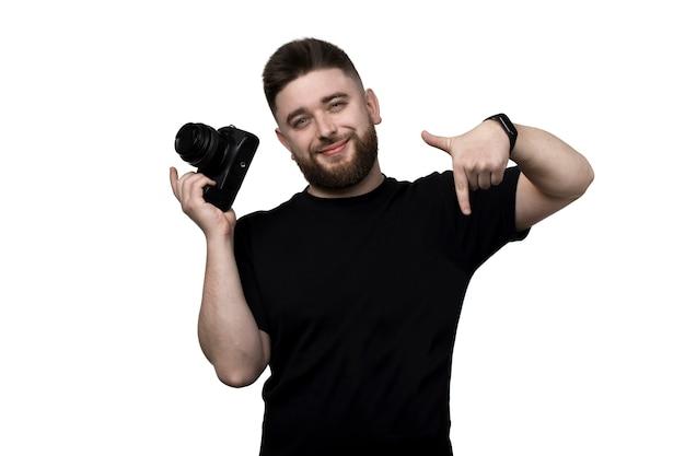 Lächelnder bärtiger fotograf, eine kamera haltend und nach unten zeigend, lokalisiert auf weißem hintergrund,