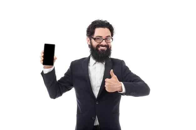 Lächelnder bärtiger geschäftsmann mit smartphone in einer hand, die wie, lokalisiert auf weißem hintergrund zeigt