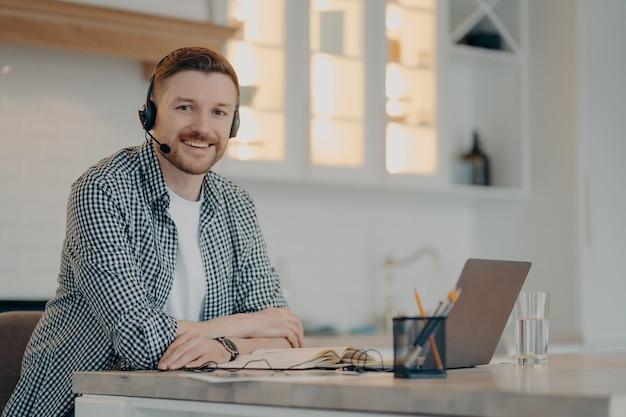 Lächelnder bärtiger, gutaussehender freiberufler, der zu hause sitzt und videoanrufe hat, während er headset und laptop verwendet, mann, der während des remote-arbeitstages zu hause in die kamera lächelt. freiberufliches konzept