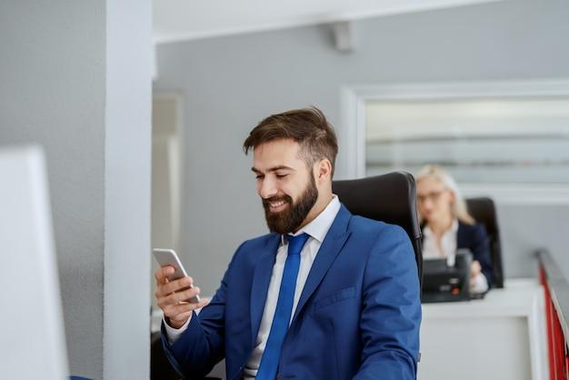 Lächelnder bärtiger kaukasischer geschäftsmann in der formellen kleidung, die an seiner arbeitsstation sitzt und smartphone benutzt. selbst der größte war einmal anfänger. haben sie keine angst, diesen ersten schritt zu tun.