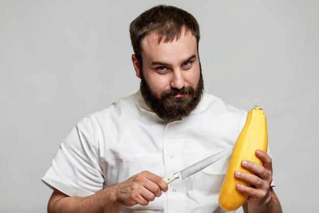 Lächelnder bärtiger männlicher koch mit messer und gelber zucchini in den händen. ein profi in einer weißen jacke ist dabei zu kochen. grauer hintergrund.