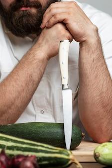 Lächelnder bärtiger männlicher koch mit messer und zucchini. ein profi in einer weißen jacke ist dabei zu kochen. grauer hintergrund. nahaufnahme. vertikal.