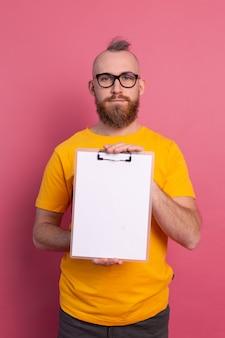 Lächelnder bärtiger mann, der brillen trägt, die freizeitkleidung tragen, die ein klemmbrett mit einem leeren papier zeigt
