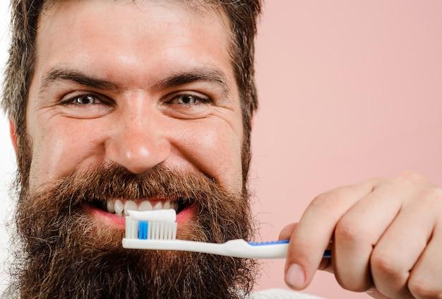 Lächelnder bärtiger mann, der die zähne putzt. zahnpasta. zahnbürste. zahnhygiene. mundpflege. nahansicht.