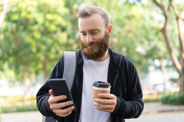 Lächelnder bärtiger mann, der in stadt geht und smartphone verwendet