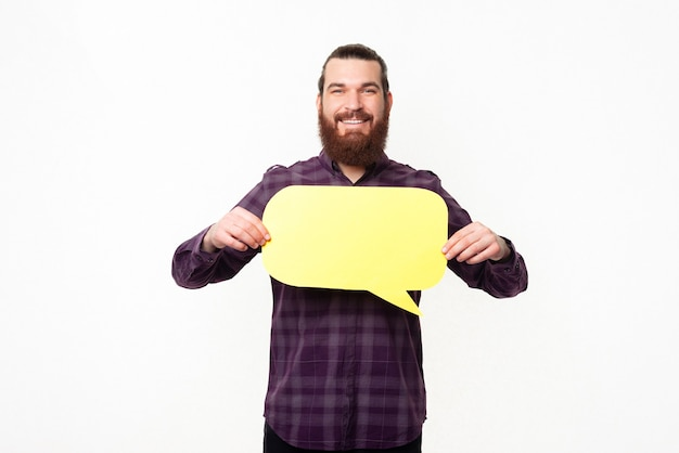 Lächelnder bärtiger mann im lässigen halten der leeren gelben sprechblase