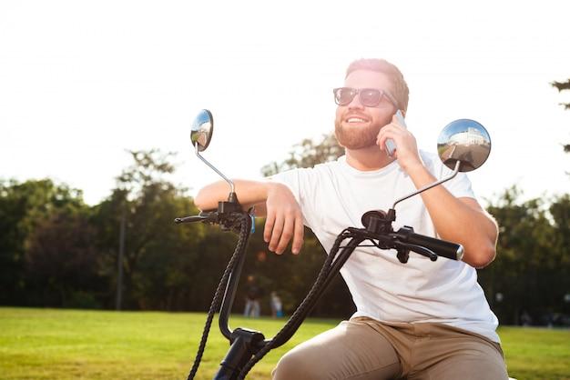 Lächelnder bärtiger mann in der sonnenbrille, die draußen auf modernem motorrad sitzt und durch das smartphone spricht