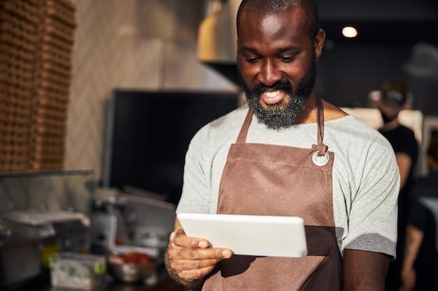 Lächelnder bärtiger mann kocht in der pizzeria und hält das touchpad beim surfen im internet während der pause surf