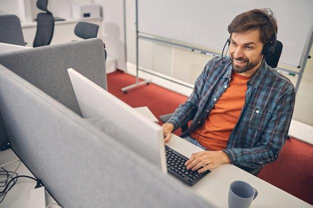 Lächelnder bärtiger mann mit headset, der am tisch sitzt und am desktop-pc arbeitet