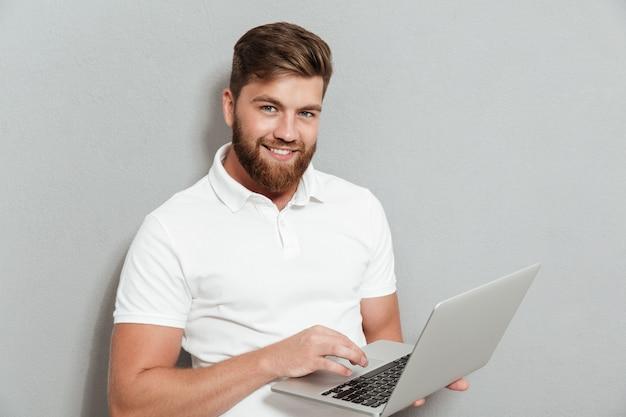 Lächelnder bärtiger mann mit laptop-computer