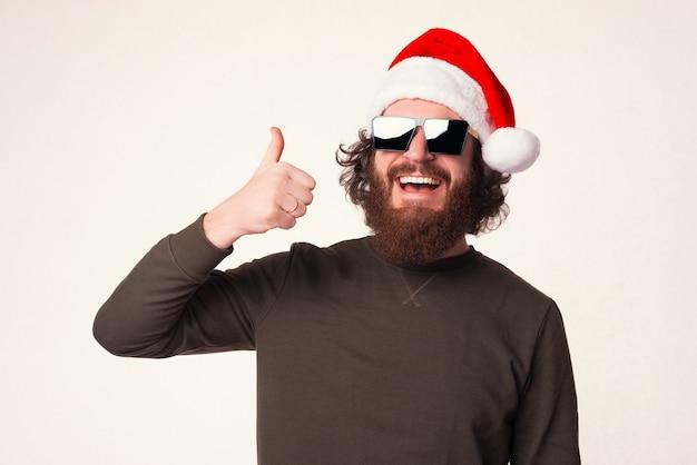Lächelnder bärtiger mann zeigt zur weihnachtszeit daumen über weißem hintergrund.