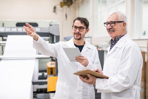 Lächelnder bärtiger qualitätsexperte für brillen, der mit der hand gestikuliert und ein tablet verwendet, während er mit einem kollegen über die produktivität der druckereiausrüstung spricht